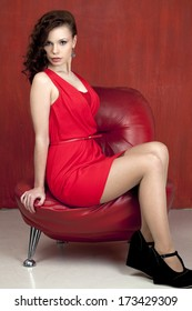 Young beautiful caucasian brunette in fashion red gown posing on red background