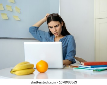 young beautiful caucasian brunette woman looking at laptop with confused and puzzled expression, frowning, being displeased with received message, wearing glasses.