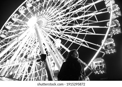 Young beautiful caucasian brunette woman posing by ferris wheel at night. Black and white photos