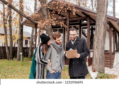 Young beautiful caucasian couple, stylish, dressed in worm outdoor apparel talking to good-looking male propery owner, businessman decides to sell a house, property investments