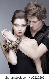 Young, beautiful caucasian couple with their hands connected with gorgeous royal python; a lot of copyspace available