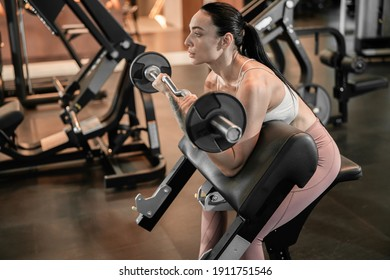 Young beautiful caucasian fit strong woman is doing exercises in gym