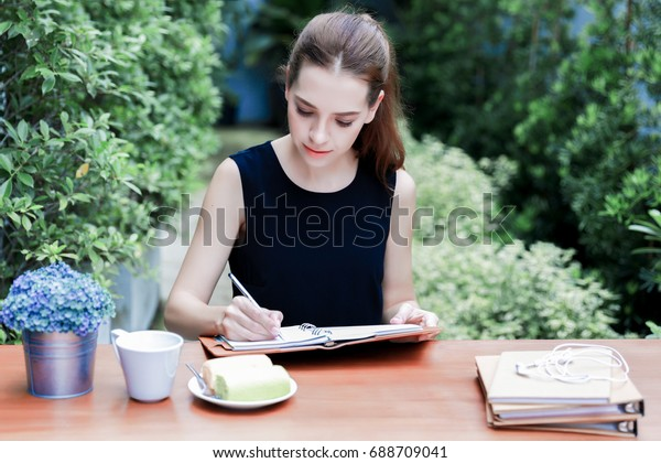 Young beautiful caucasian girl enjoy writing a diary book with happily face in the garden.