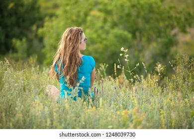 Young and beautiful caucasian girl with long hair in sunglasses sits in the meadow on a sunny day. Pretty woman is sitting on the grass and resting.