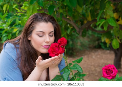 Young beautiful Caucasian girl smelling the roses in the garden.