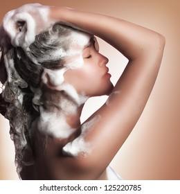 young beautiful caucasian girl soaping her head