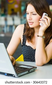 young beautiful caucasian girl talking on phone while using laptop