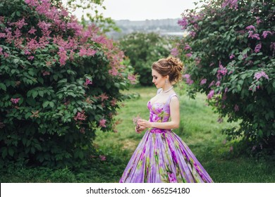 Young beautiful caucasian girl in vintage evening dress in blossom lilac garden.