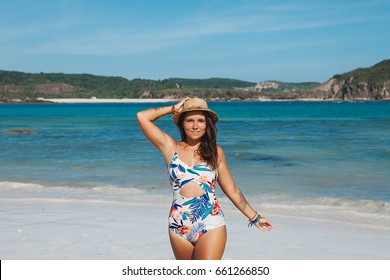 Young beautiful caucasian girl wearing one piece swimsuit and straw hat enjoy vacation on white sand beach during travel in Asia, Bali. Globetrotter blogger, leisure and discover