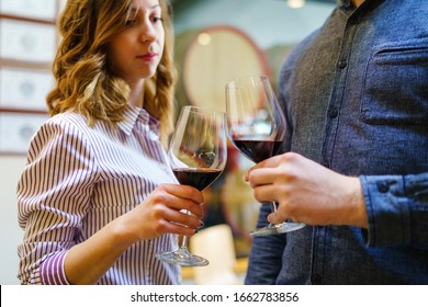 Young beautiful caucasian girl woman toasting to unknown man while standing and holding a glasses of red wine selective focus at home or winery