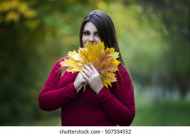 Young beautiful caucasian plus size model in red pullover outdoors, woman on nature, autumn atmosphere, women