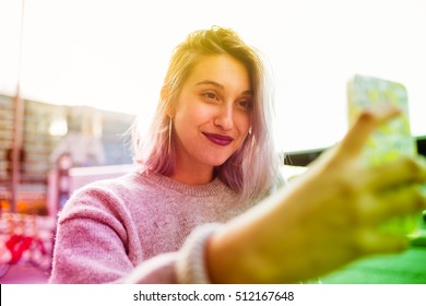Young beautiful caucasian purple grey hair woman outdoor in the city outdoor in city back light taking selfie with smart phone hand hold - vanity, social network, sharing concept