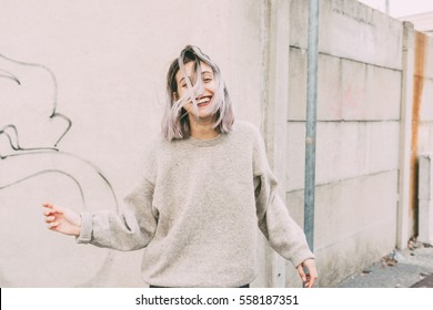 Young beautiful caucasian purple grey hair woman outdoor in the city dancing having fun - happiness, freedom, dancing concept