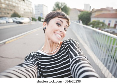 Young beautiful caucasian short hair woman taking selfie outdoor - traveler, vanity, social network concept