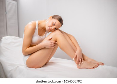 joven caucásica mujer joven después de la epilación láser y la cosmetología en el salón de belleza. procedimiento de eliminación del cabello en piernas, caderas. epilepsia láser, cosmetología, spa y concepto de depilación
