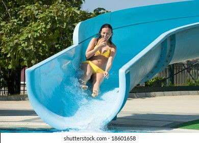 Young beautiful caucasian woman in bikini on swimming pool water slide