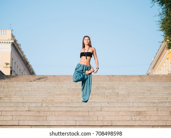 Young beautiful caucasian woman doing yoga asana in the city stairs. Summer morning.