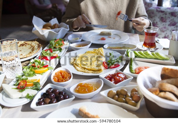 Young Beautiful Caucasian Woman Having Traditional Turkish Breakfast at Lovely Hotel, Cafe Restaurant in Sunny Day siting near the window table. Healthy Eating for peaceful life.