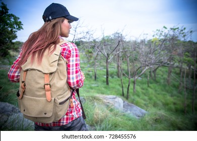 Young beautiful Caucasian woman hipster girl hike climbing up hill, with backpacks. Female tourist hiker Hiking standing on top of mountain. looking at scenic view. feeling happy, successful concept.