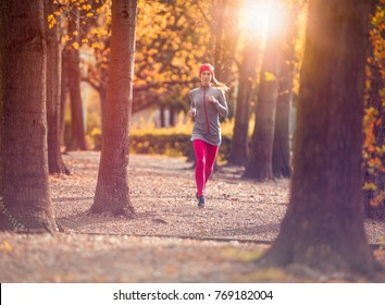 young beautiful caucasian woman jogging workout training. Autumn running fitness girl in city urban park environment with fall trees orange. Sunset or sunrise warm light. Sport activity in cold season