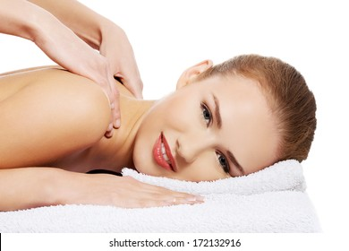 Young beautiful caucasian woman lying on a massage table and is being massaged. Isolated on white.