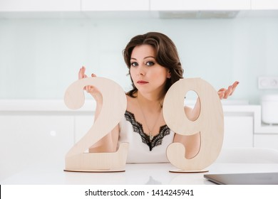 Young beautiful Caucasian woman on a white modern kitchen with wooden signs in the form of numbers 29. Numerology, meaning of numbers, magic