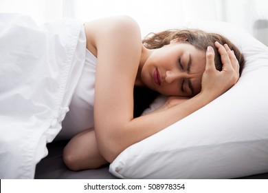 Young beautiful Caucasian woman on bed having headache / insomnia / migraine / stress