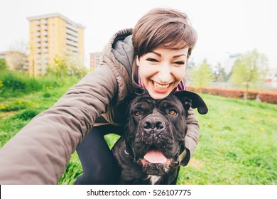 Young beautiful caucasian woman in a park outdoor taking selfie with her dog - happiness, friendship concept