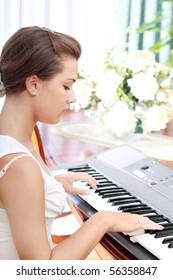 Young beautiful Caucasian woman playing on electric piano