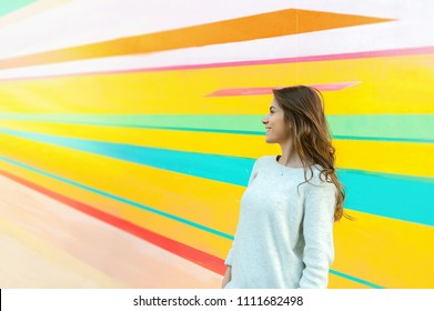 Young beautiful caucasian woman posing outdoor in the city, near a colorful wall.