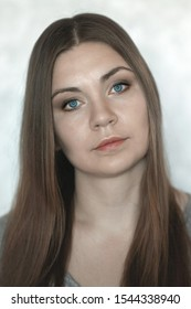 Young beautiful caucasian woman with realistic beauty and strong individuality looks right up to the camera. Bright blue eyes, dark blonde hair, serious attentive look. Indoors, copy space.
