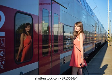 Young beautiful caucasian woman with a suitcase next to the train wearing casual summer clothes.