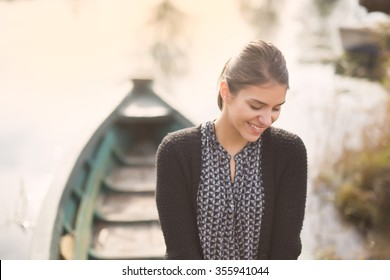 Young beautiful charming woman at the old fishing boat smiling.Honest reaction on a  male complimenting.Compliment concept.Paying a compliment beautiful woman