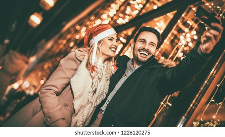 Young beautiful cheerful couple taking a selfie in the city street at new year's night with a lot of lights on background.
