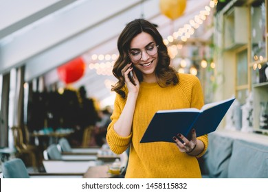 Young beautiful cheerful dark haired woman wearing warm yellow sweater planning party talking on phone holding blue notebook in hand