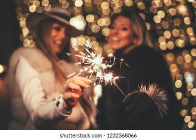 Young beautiful cheerful female friends with sparklers having fun and enjoying in the city street at Christmas eve. Selective focus. Focus on foreground, on sparklers.