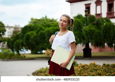 Young beautiful cheerful female student smiling, holding folders outdoors, park background.