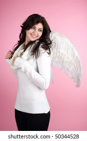 Young beautiful cheerful girl in angel suit over pink background.