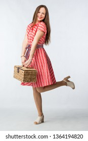 Young beautiful cheerful woman in red dress posing with picnic basket in studio on white background