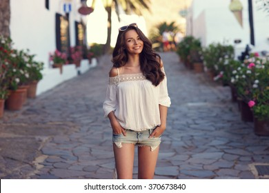 Young beautiful cheerful woman walking on old street at tropical town. Pretty girl looking at you and smiling