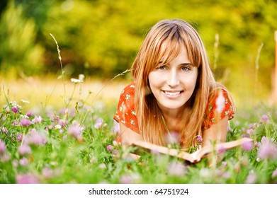 Young beautiful cheerful woman-student in red dress lies on green summer meadow with clover and reads textbook.