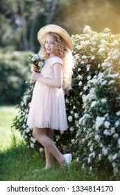 young beautiful child girl in blooming spring garden. flowers