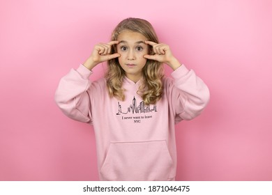 Young beautiful child girl standing over isolated pink background Trying to open eyes with fingers, sleepy and tired for morning fatigue