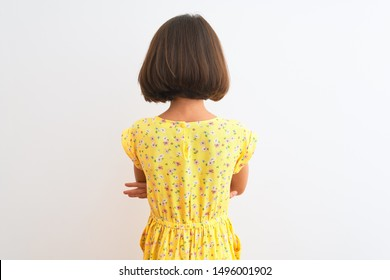 Young beautiful child girl wearing yellow floral dress standing over isolated white background standing backwards looking away with crossed arms