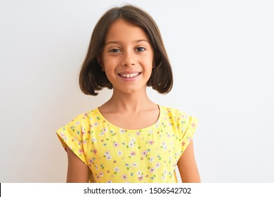 Young beautiful child girl wearing yellow floral dress standing over isolated white background with a happy face standing and smiling with a confident smile showing teeth
