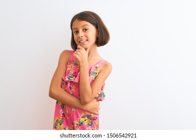 Young beautiful child girl wearing pink floral dress standing over isolated white background looking confident at the camera smiling with crossed arms and hand raised on chin. Thinking positive.