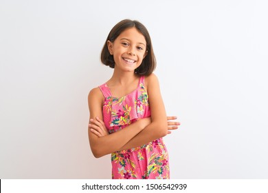 Young beautiful child girl wearing pink floral dress standing over isolated white background happy face smiling with crossed arms looking at the camera. Positive person.