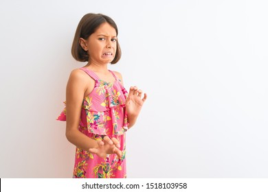 Young beautiful child girl wearing pink floral dress standing over isolated white background disgusted expression, displeased and fearful doing disgust face because aversion reaction.
