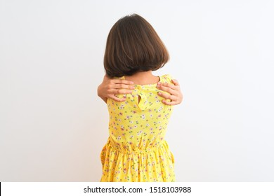 Young beautiful child girl wearing yellow floral dress standing over isolated white background Hugging oneself happy and positive from backwards. Self love and self care