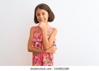 Young beautiful child girl wearing pink floral dress standing over isolated white background looking confident at the camera with smile with crossed arms and hand raised on chin. Thinking positive.